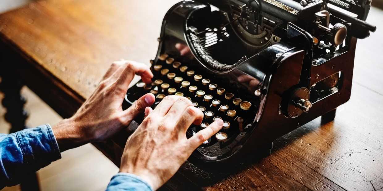 Mann schreibt auf alter Schreibmaschine